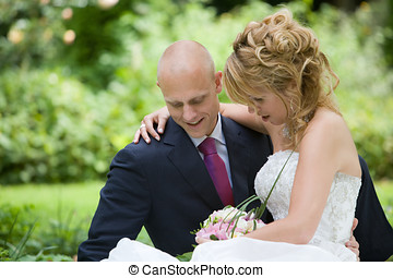 Relaxing moment - Beautiful bride and groom sitting on a...