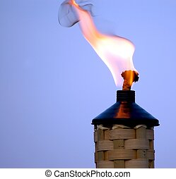 Tiki torch at dusk during a cookout