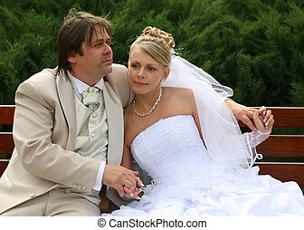 Newly married pair - Recently married pair sits on a bench...