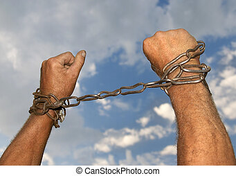 Bondage - Hands with chains around them on sky background