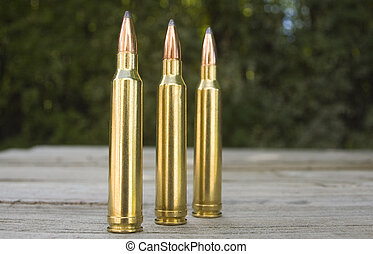 Bullets - Three 30-06 bullets sit on a table