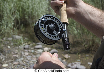 Flyfishing Reel - A flyfisherman pulls line from his reel.
