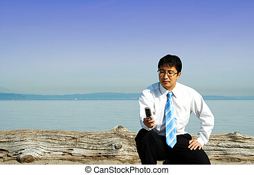 Businessman - A businessman checking on his cell phone at...