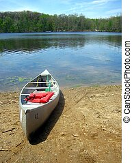 Lakeside Canoe - A canoe beached on the shore of a lake.