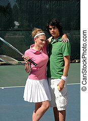 Tennis Couple - A yonng couple embracing on the tennis court