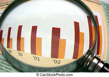 Business Focus - A magnifying glass focusing on a graph in...