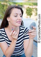 woman put on lipstickr - young woman put on lipstick