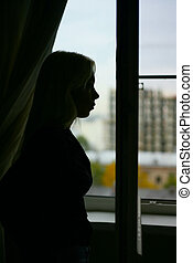 Silhouette of the girl on a background of a window