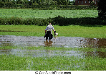 Wading Man - Man wading through flood waters on farmland...