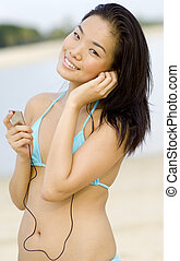 Beach Babe - A young pretty Asian woman with mp3 player on...
