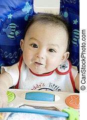 Baby Boy (6-9 Months) Sitting in High Chair With Food on Face