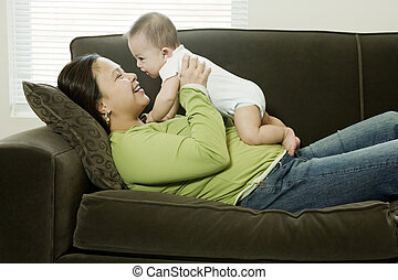Mother Holding Up Baby Boy (6-9 Months), Smiling at Baby