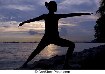 Warrior Pose - A young Asian woman doing a warrior pose at...