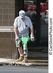 Man using jack hammer - Construction company removing curb...