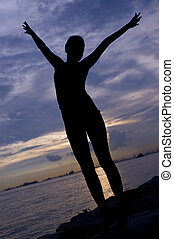 Stretching - A silhouette of a young woman stretching beside...