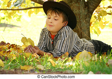 Child holding autumn leaves - A child resting under a...