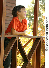 Enjoying Country Life - Happy child leaning on the porch...
