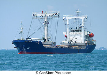 Bulk ship at anchor - Blue bulk ship at anchor in tropical...