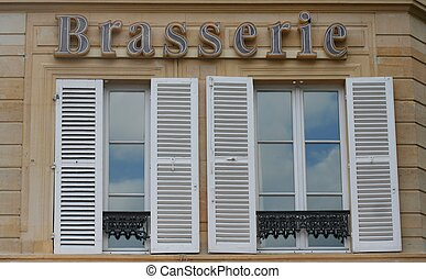 French brasserie sign on a building with shutters