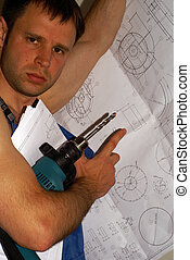 A handsome construction worker with a drawing and tool in...