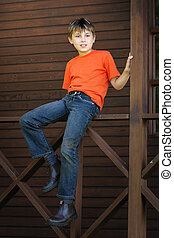 Boy sitting on the verandah - A child sits on the timber...