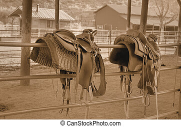 Wild West - horse saddles hanging over stable fence