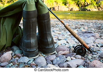 Waders - A pair of waders sit along a river bed with a...
