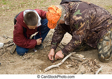 Survival instructor assisting student to start fire - Hunter...