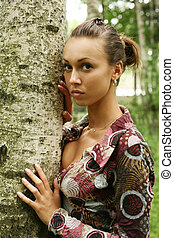 In forest - Young woman leaning against birch tree in forest