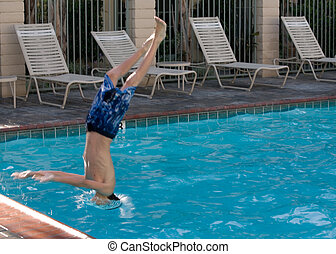 Diving into the pool - Young boy diving head first into a...