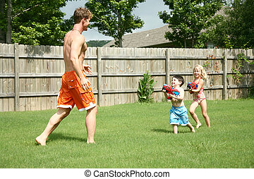 Boy and Girl with Waterguns - Boy and girl chase dad with...
