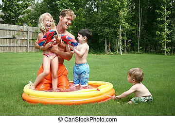 Boys and girl play with dad in the kiddie pool with water...