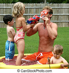 Boys and girl play with dad in the kids pool - Boys and girl...
