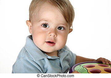 Adorable baby boy in blue shirt on spin toy