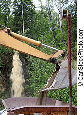 Gold Panning - modern - A back hoe pours dirt to be washed...