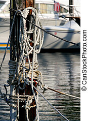 Tied Up - Rope tied to a post holding boats against the...