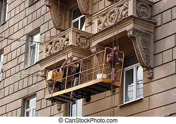 restoring  - Two workers restoring old city building