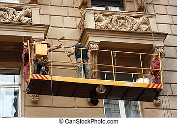 restoring  - Two workers restoring old city building by tool