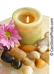 Fragances - Lit candle with pebbles and flowers