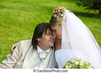 Newly married pair - Recently married pair sits on a grass...