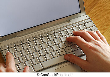 blogger - close up of hands typing on laptop computer...