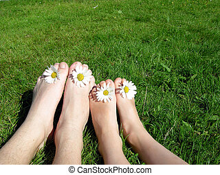 Happy summer feet - Two children sitting on the grass with...