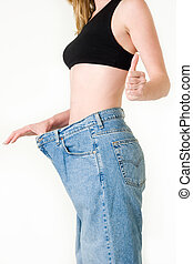 Achievement - Woman demonstrating weight loss by wearing an...