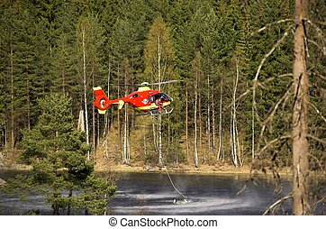 Water Rescue - A red Norwegian Air Ambulance helicopter...