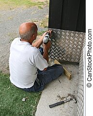 Caretaker - Man attaching a aluminum plate on a wall