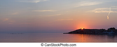 Sunset on sea with cape in distance