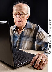Intellectual senior man works on the laptop late at night