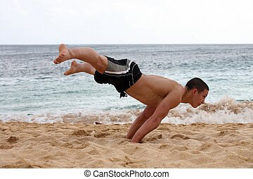 Handstand on the beach - Young man doing handstand on the...