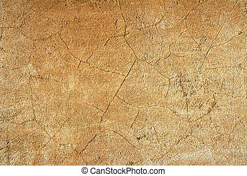 cracked stucco - close up of ochre colored cracked stucco...