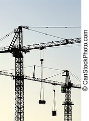 cranes vertical - two cranes silhouetted against evening...